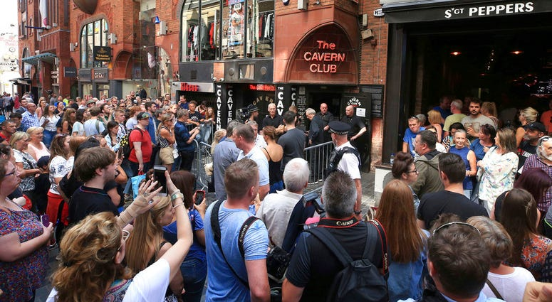 People queue outside the Cavern Club in Liverpool, England, before an exclusive gig by former Beatles member Paul McCartney, Thursday July 26, 2018.