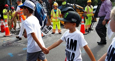 Construction workers watch as children hold hands during a march in protest of the separation of immigrant families, Thursday, July 26, 2018, on Capitol Hill in Washington.