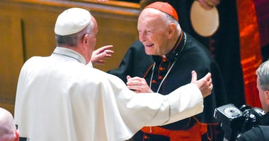 In this Sept. 23, 2015 file photo, Pope Francis reaches out to hug Cardinal Archbishop emeritus Theodore McCarrick after the Midday Prayer of the Divine with more than 300 U.S.