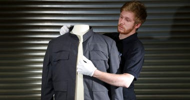 """Prop Store employee James Chapman adjusts Han Solo's jacket, as worn by Harrison Ford in """"Star Wars: The Empire Strikes Back."""""""