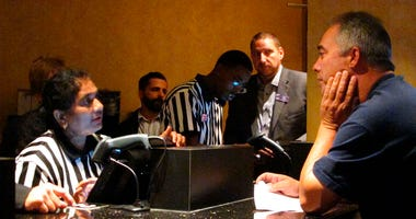 A clerk at the new sports book at Harrah's casino in Atlantic City N.J. process wagers for a customer moments after the casino started accepting sports bets on Wednesday Aug. 1, 2018.