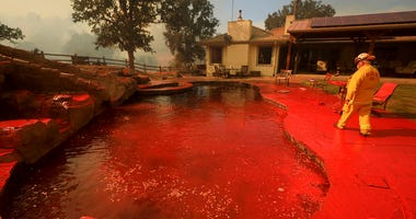A firefighter walks around a swimming pool sprayed by phos-chek fire retardant after an air tanker made a pass while fighting a wildfire near Lakeport, Calif., Thursday, Aug. 2, 2018.