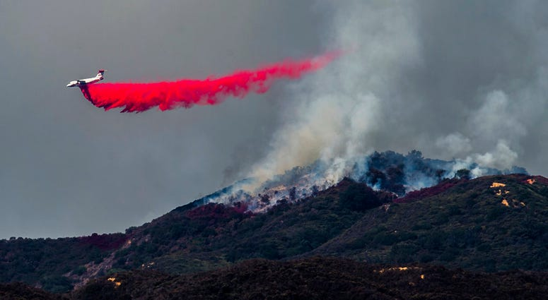 A plane drops fire retardant as firefighters continue to battle a wildfire in the Cleveland National Forest near Corona, Calif. on Tuesday, Aug. 7, 2018.