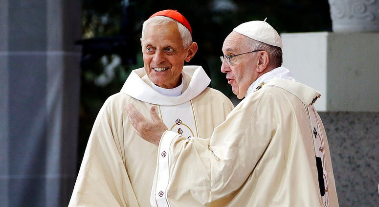 In this Sept. 23, 2015, file photo, Cardinal Donald Wuerl, archbishop of Washington, left, looks toward the crowd with Pope Francis following a Mass outside the Basilica of the National Shrine of the Immaculate Conception in Washington.