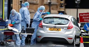 Forensics officers work near the car that crashed into security barriers outside the Houses of Parliament in London, Tuesday, Aug. 14, 2018.