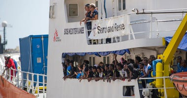 Migrants and members of the crew of the Aquarius rescue ship wave as they enter the harbor of Senglea, Malta, Wednesday, Aug. 15, 2018.