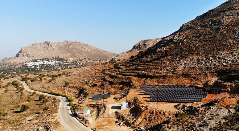 In this Thursday, Aug. 9, 2018, photo a road leads past a solar park on the Aegean island of Tilos, Greece.