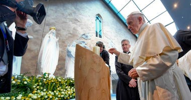 Pope Francis lights a candle as he visits the Knock's shrine during his apostolic trip to Ireland, Sunday, Aug. 26, 2018.