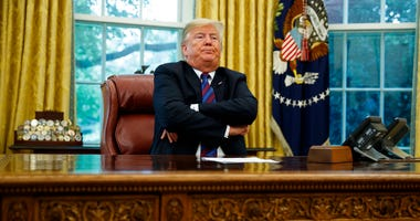 President Donald Trump crosses his arms after speaking with Mexican President Enrique Pena Nieto on the phone about a trade agreement between the United States and Mexico, in the Oval Office of the White House, Monday, Aug. 27, 2018, in Washington.