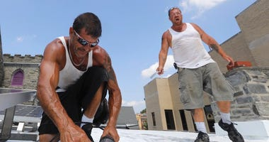 Roofers Ricky Yarnall, left, and Mike Oakes are convinced it is 40 degrees hotter on the top of the Central Baptist Church in Wayne, Pa. as they work through Wednesday afternoon, Aug. 29, 2018.