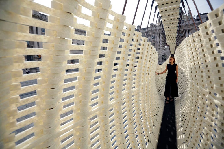 """The Greek exhibit """"Disobedience"""", with designer Nassia Inglessis posing, a 17 metre-long wall constructed from a steel spring skeleton built up with recycled plastic which flexes, is displayed during a preview for the London Design Biennale."""