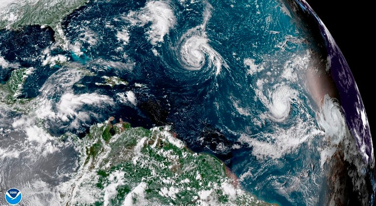 This enhanced satellite image made available by NOAA shows Tropical Storm Florence, center, in the Atlantic Ocean on Saturday, Sept. 8, 2018 at 2:45 p.m. EDT.