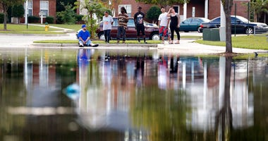 Residents look out at the flooded entrance to an apartment complex in Fayetteville, N.C.