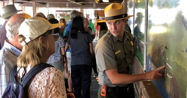 In this Saturday, Sept. 22,2018, photo released by the National Park Service shows tourists get directions on the first day Hawaii Volcanoes National Park is reopened after volcanic activity forced the park to close for more than four months in Hawaii.