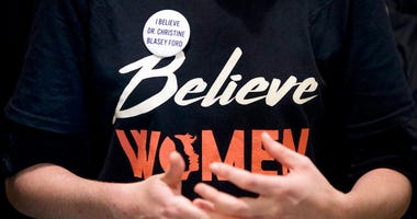 "A woman wears a shirt that reads ""Believe Women."""