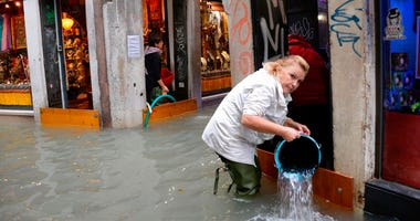 A woman removes water from a shop in a flooded street of Venice, Italy, Monday, Oct. 29, 2018, as, according to city officials, 70 percent of the lagoon city has been flooded by waters rising 149 centimeters (more than 58 1/2 inches) above sea level.