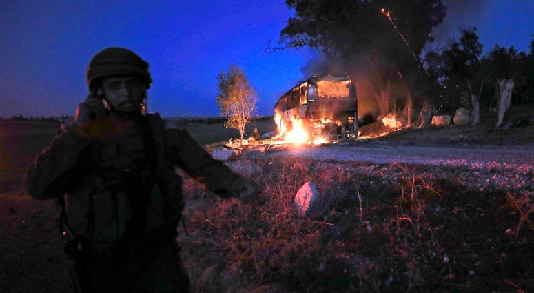 An Israeli soldier stands near a burning bus after it was hit by a mortar shell fired from Gaza near the Israel Gaza border, Monday, Nov. 12, 2018.