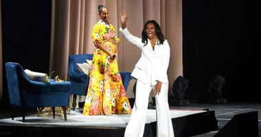 """Former first lady Michelle Obama greets the audience as Tracee Ellis Ross watches at the """"Becoming: An Intimate Conversation with Michelle Obama"""" event at the Forum on Thursday, Nov. 15, 2018, in Inglewood, Calif."""