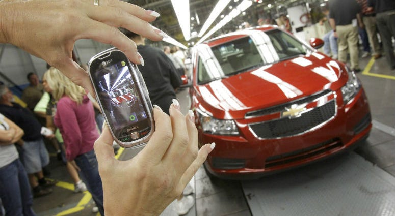 FILE - In this Sept. 8, 2010 file photo, auto worker Brenda Hedland takes a picture of the first Chevrolet Cruze compact sedan to come off the assembly line at a ceremony inside the GM factory in Lordstown, Ohio.