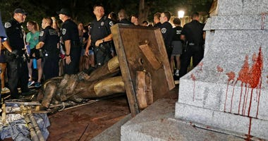 FILE - In this Aug. 20, 2018, file photo, police stand guard after the confederate statue known as Silent Sam was toppled by protesters on campus at the University of North Carolina in Chapel Hill, N.C.