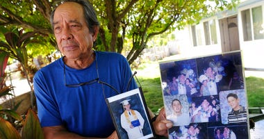 FILE - In this July 10, 2017, file photo, Clifford Kang, father of soldier Ikaika E. Kang, poses with photos of his son in Kailua, Hawaii.