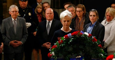 Cindy McCain, center, widow of the late U.S> Sen. John McCain, R-Ariz., views the flag-draped casket of former President George H.W. Bush as he lies in state in the Capitol Rotunda in Washington, Tuesday, Dec. 4, 2018.