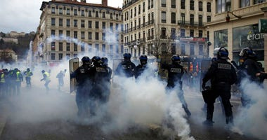 Police officers clash with demonstrators in Lyon, central France, Saturday, Dec. 8, 2018.