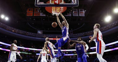 Philadelphia 76ers' Ben Simmons (25) dunks the ball past teammate Joel Embiid (21) as Detroit Pistons' Bruce Brown (6) and Luke Kennard (5) watch during the first half of an NBA basketball game, Monday, Dec. 10, 2018, in Philadelphia.