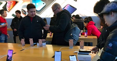 People buy latest iPhone while others try out its latest model at an Apple Store in Beijing, Tuesday, Dec. 11, 2018.