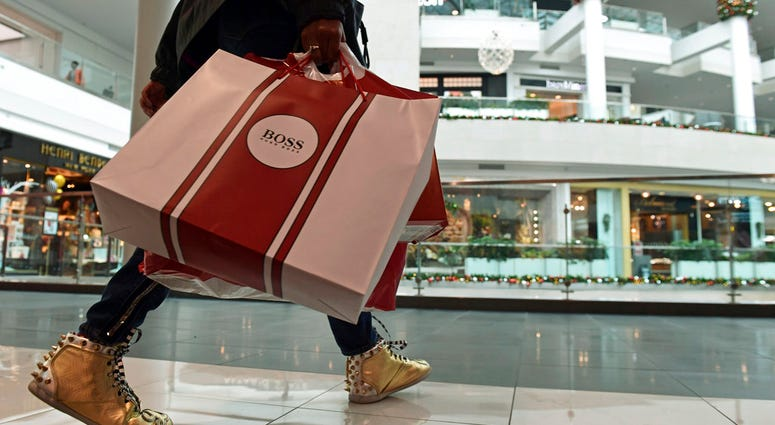 In this Dec. 22, 2017, file photo, people shop at the Pentagon City Mall in Arlington, Va.