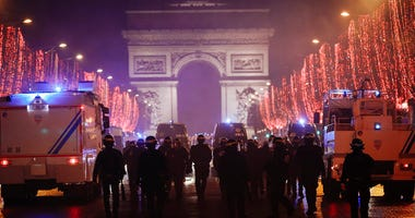Riot police officers are seen on the Champs Elysees avenue with the Arc de Triomphe in the background, during a demonstration, in Paris Saturday, Dec. 22, 2018.