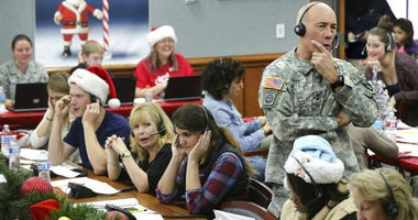 FILE - In this Dec. 24, 2014, file photo, NORAD Chief of Staff Maj. Gen. Charles D. Luckey takes a call while volunteering at the NORAD Tracks Santa center at Peterson Air Force Base in Colorado Springs, Colo.
