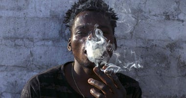 FILE - In this Tuesday, Sept. 18, 2018, file photo, a Malawian migrant Jonas smokes marijuana on the rooftop of an abandoned building in downtown Johannesburg.
