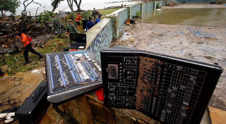 A rescue team walks near an audio mixer damaged by a tsunami at Tanjung Lesung beach resorts Indonesia, Monday, Dec. 24, 2018.