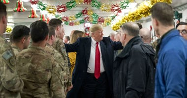 President Donald Trump visits with members of the military at a dining hall at Al Asad Air Base, Iraq, Wednesday, Dec. 26, 2018.