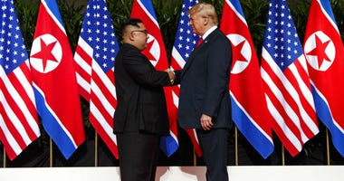 FILE - In this June 12, 2018, file photo, North Korean leader Kim Jong Un, left, and U.S. President Donald Trump shake hands prior to their meeting on Sentosa Island in Singapore.