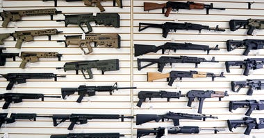 Semi-automatic rifles fill a wall at a gun shop.