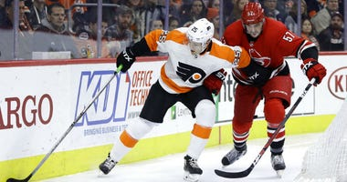 Philadelphia Flyers' James van Riemsdyk, left, tries to keep Carolina Hurricanes' Trevor van Riemsdyk away from the puck during the second period of an NHL hockey game Thursday, Jan. 3, 2019, in Philadelphia.