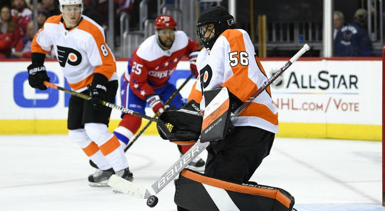 Philadelphia Flyers goaltender Mike McKenna (56) stops the puck during the second period of an NHL hockey game as Washington Capitals right wing Devante Smith-Pelly (25) watches, Tuesday, Jan. 8, 2019, in Washington.