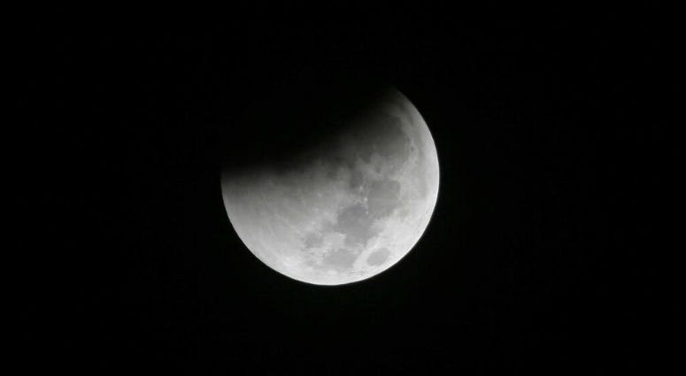 FILE - In this Saturday Aug. 28, 2018 file photo, Earth starts to cast its shadow on the moon during a complete lunar eclipse seen from Jakarta, Indonesia.