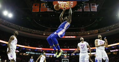 Philadelphia 76ers' Joel Embiid, center, hangs on the rim after a dunk during the first half of an NBA basketball game against the Minnesota Timberwolves, Tuesday, Jan. 15, 2019, in Philadelphia.