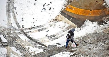 A pedestrian walks across the street in downtown Scranton, Pa., on Sunday, Jan. 20, 2019.