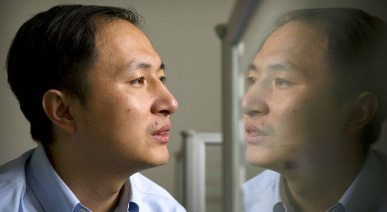 FILE - In this Oct. 10, 2018, file photo, He Jiankui is reflected in a glass panel as he works at a computer at a laboratory in Shenzhen in southern China's Guangdong province.