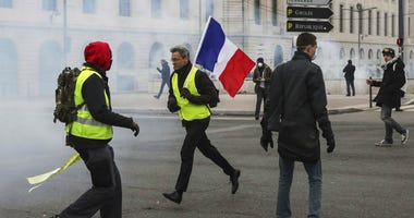 A demonstrator carries a French flag as yellow vest demonstrators are hit by tear gas during clashes in Lyon, central France, Saturday, Jan. 26, 2019.