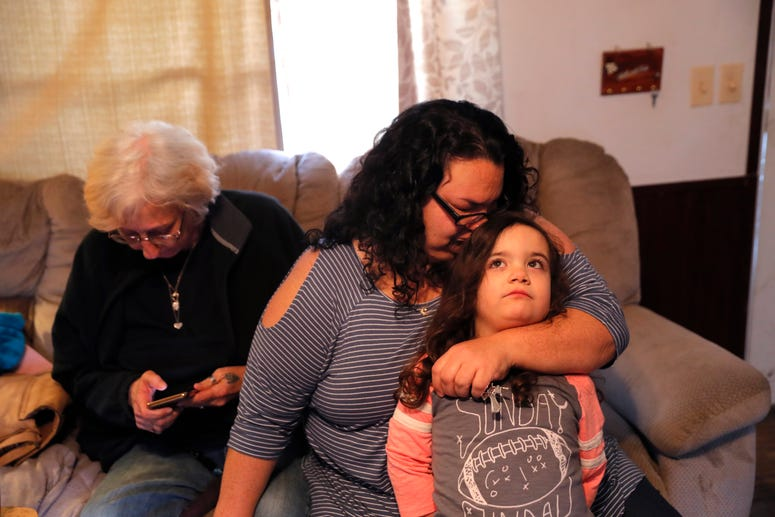 Tina Chastant hugs her daughter Rosalina Chastant, 5, in Gonzalez, La., Sunday, Jan. 27, 2019, after they arrived to comfort Kim Mincks, left, after two people were found dead inside the home yesterday.