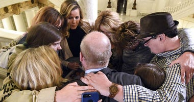 FILE- In this file photo from Oct. 17, 2018, survivors of child sexual abuse hug in the Pennsylvania Capitol in Harrisburg, Pa.
