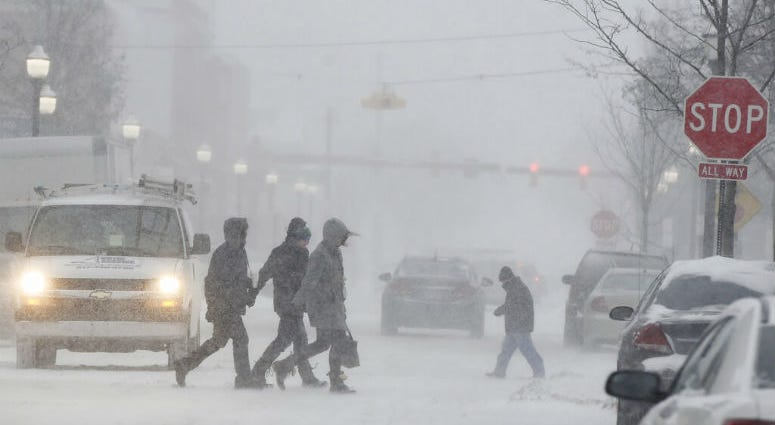 People walk through a snowstorm in downtown Jackson, Mich., Monday, Jan. 28, 2019.