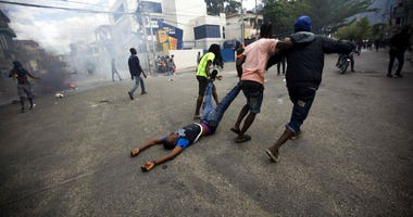 Demonstrators drag the body of a fellow protester toward police, as a form of protest after police shot into the crowd in which he died, during a demonstration demanding the resignation of Haitian President Jovenel Moise near the presidential palace in Po