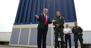 FILE - In this March 13, 2018, file photo, President Donald Trump talks with reporters as he reviews border wall prototypes in San Diego.