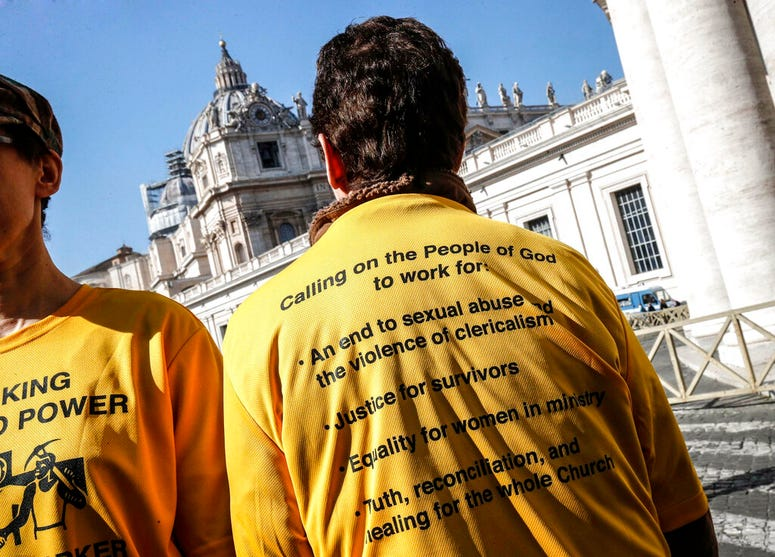 Demonstrators wear shirts as they stand outside St. Peter's Square on the day of the opening of a sex abuse within the Catholic church prevention summit, at the Vatican, Thursday, Feb. 21, 2019.